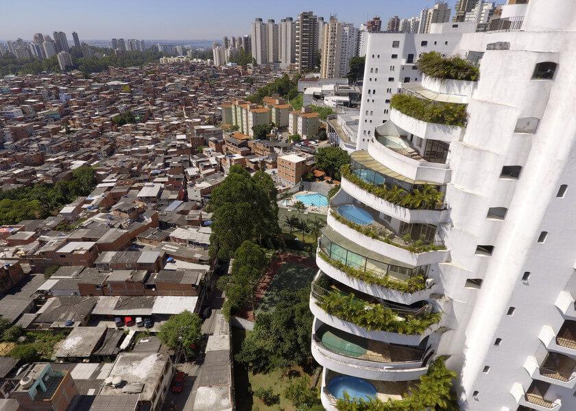 Do lado esquerdo, vemos parte da Favela de Paraisópolis, em São Paulo, do lado direito, vemos um dos vários condomínios de luxo da região do Morumbi.