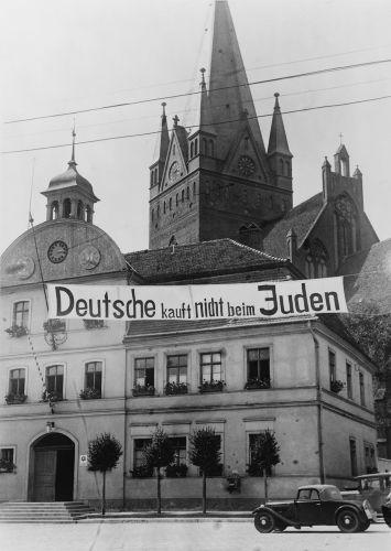 """Na faixa está escrito """"Alemães não compram em lojas de judeus"""". O antissemitismo na sociedade alemã levou ao genocídio conhecido como Holocausto. [1]"""