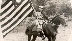 Soldado em um cavalo com uma bandeira