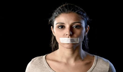 Mulher com a boca tapada com fita adesiva