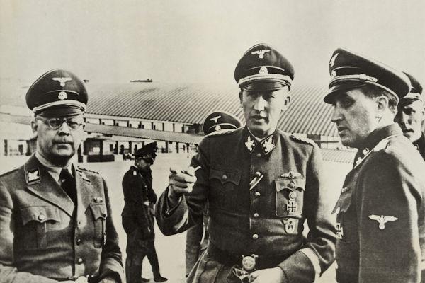 Heinrich Himmler (à esquerda, de óculos) foi um dos responsáveis por ampliar a atuação da Gestapo por toda a Alemanha.[2]