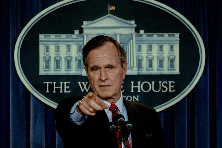 George H. W. Bush em púlpito presidencial apontado o dedo em direção à sua frente