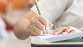 Aluna escrevendo em caderno e sentada em carteira
