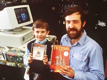 """Pajitnov mostrando várias versões do jogo """"Tetris"""" ao lado de um provável fã"""
