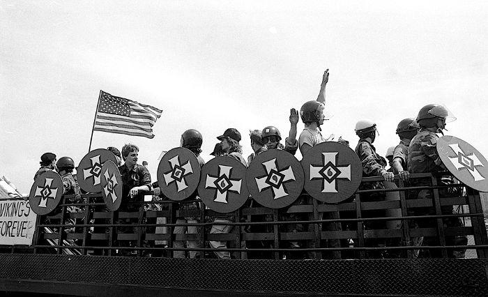 Supremacistas brancos em manifestação realizada em Chicago, em 1986. A cruz no escudo é o símbolo do emblema da Ku Klux Klan.**