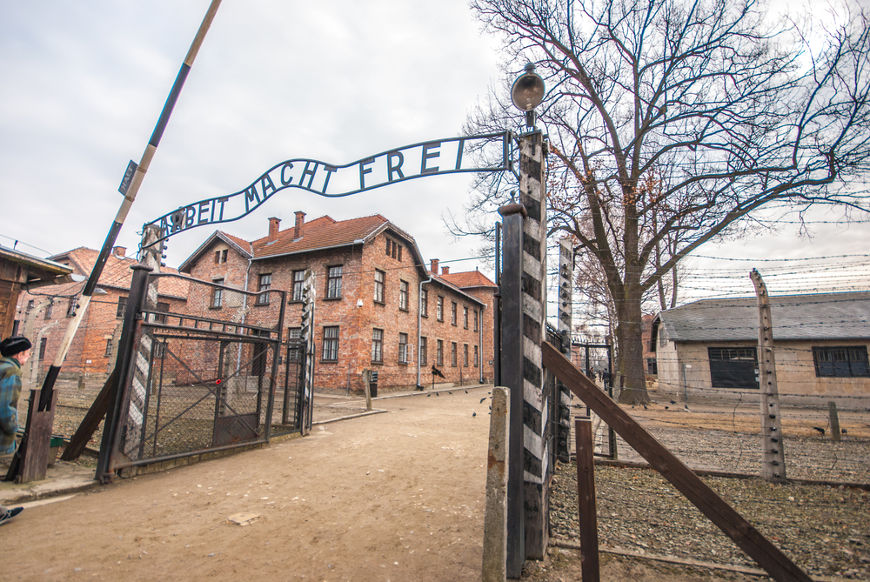 """Portal de entrada de Auschwitz, o maior campo de extermínio nazista. No portal está escrito """"o trabalho liberta""""."""