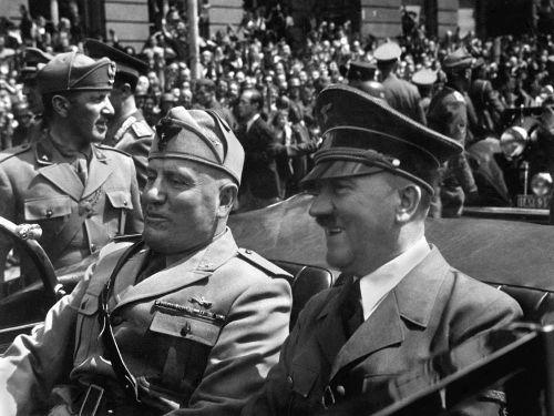 Benito Mussolini (à esquerda) desfilando em carro aberto ao lado de Adolf Hitler