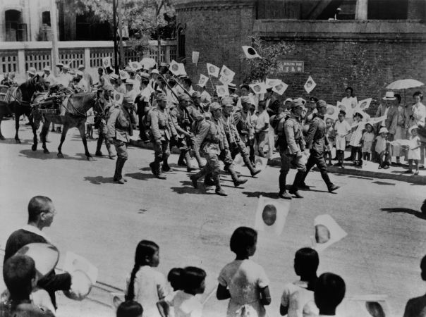 Cidadãos japoneses saudando os soldados japoneses em sua chegada a cidade de Pequim