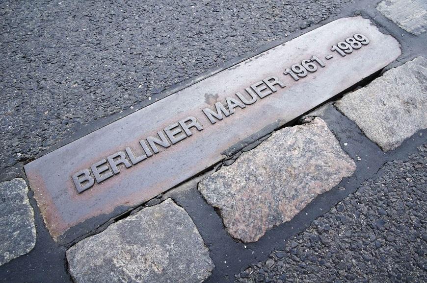 Placa no solo sinalizando onde foi construída parte do muro de Berlim